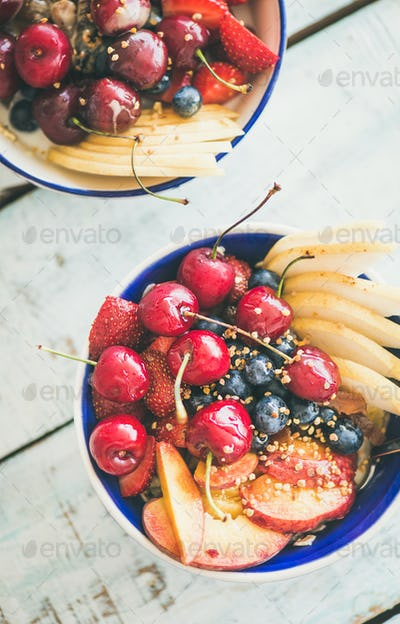 Smoothie bowl with fruit and berries, wooden background, top view