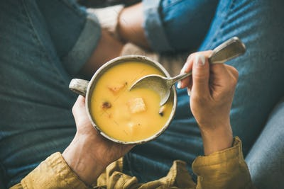 Female sitting keeping mug of Fall warming pumpkin cream soup