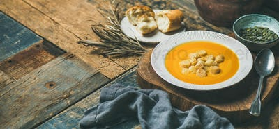 Warming pumpkin cream soup with croutons and seeds, wide composition