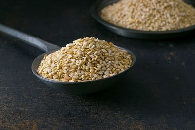A metal spoon full of sesame seeds