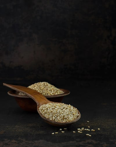 A wooden spoon and bowl of sesame seeds