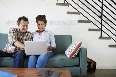 Senior Couple Sitting On Sofa At Home Using Laptop Together