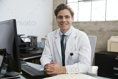 Young white male doctor at desk, portrait
