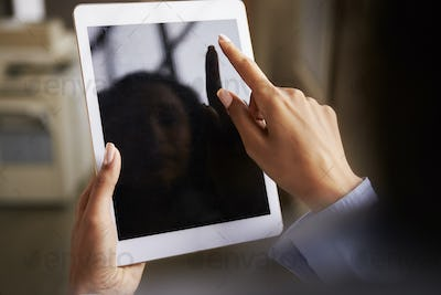 Close up of womanÕs hands using tablet touchscreen