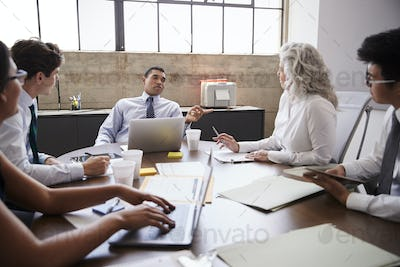 Male manager brainstorming with team in meeting room