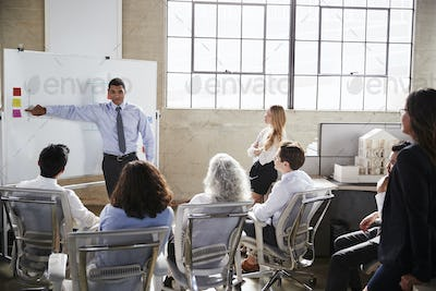 Businessmastands using whiteboard during a presentation