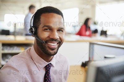 Man working in a call centre smiling to camera, close-up
