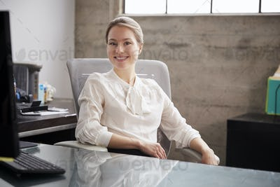 Young white woman sitting at office desk smiling to camera