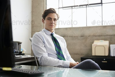 Young white businessman at an office desk looking to camera