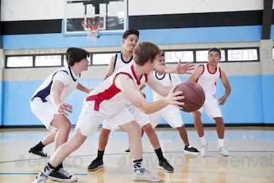 Male High School Basketball Team Dribbling Ball On Court