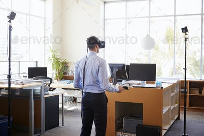 Businessman using VR technology in an office, back view