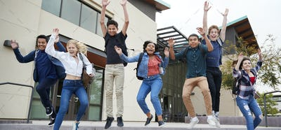 Group Of High School Students Jumping In Air Outside College Buildings