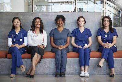 Female healthcare workers sitting in a hospital, full length