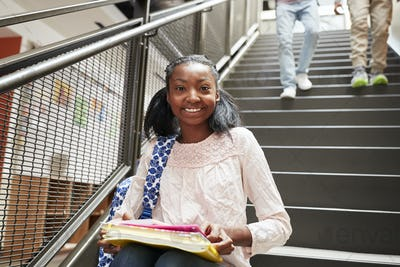 Portrait Of Female High School Student Sitting On Stairs In College Building