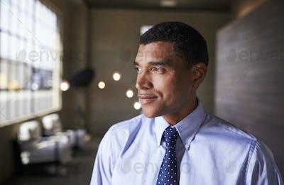 Mixed race businessman looking away smiling, close up