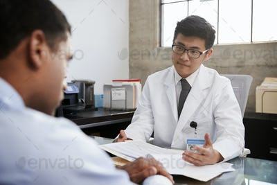 Young Asian male doctor in consultation with male patient