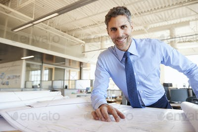 Male architect studying plans looking to camera, close up