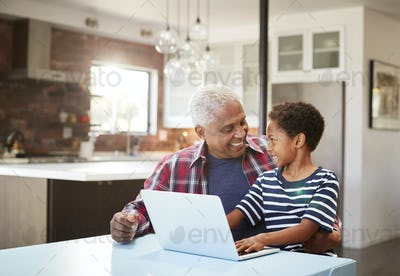 Grandfather And Grandson Sitting Around Table At Home Using Laptop Together