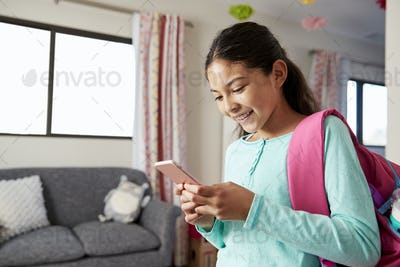 Young Girl With Backpack In Bedroom Ready To Go To School Checking Mobile Phone