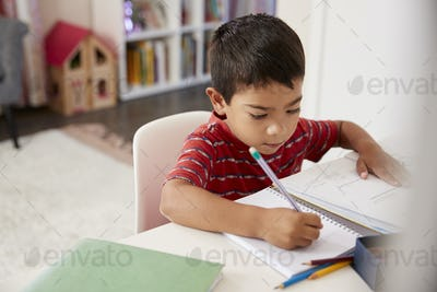 Young Boy Sitting At Desk In Bedroom Doing Homework