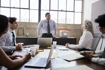 Male manager stands listening to team in brainstorm meeting