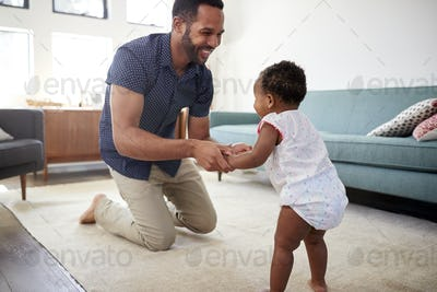 Father Encouraging Baby Daughter To Take First Steps At Home