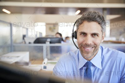 White male call centre worker smiling to camera