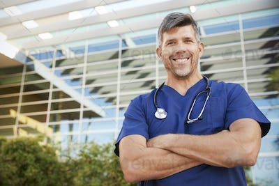 Happy male healthcare worker smiling to camera outdoors