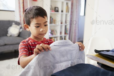 Boy In Bedroom Choosing Shirt Ready For School