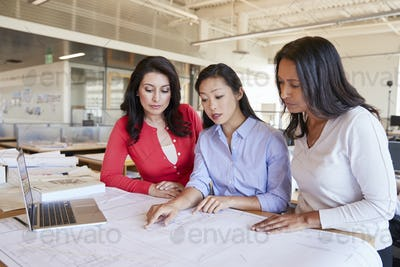 Three female architects studying plans together in an office