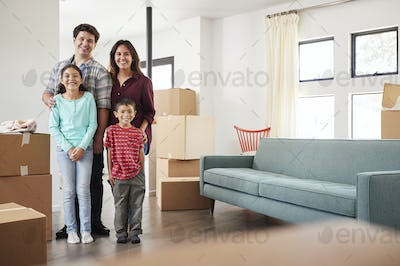 Portrait Of Happy Family Surrounded By Boxes In New Home On Moving Day