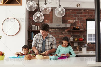Children Helping Father To Make School Lunches In Kitchen At Home