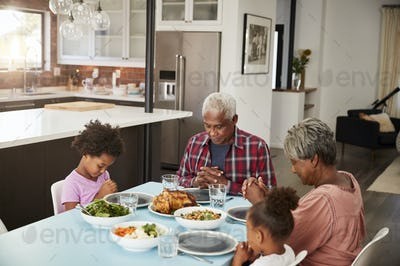 Grandparents Praying Before Meal At Home With Granddaughters