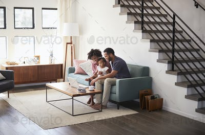 Family With Baby Daughter Sitting On Sofa At Home Looking At Laptop Computer