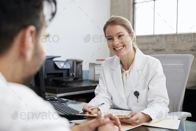 Smiling female doctor in consultation with male patient