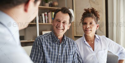 Senior Couple Meeting With Male Financial Advisor At Home