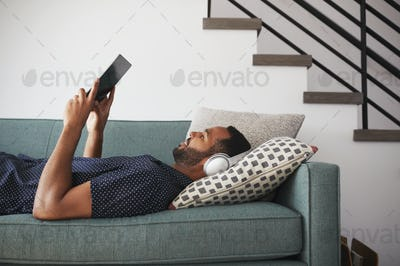 Man Lying On Sofa At Home Wearing Headphones And Watching Movie On Digital Tablet