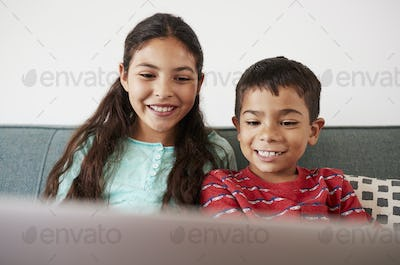 Brother And Sister Sitting On Sofa At Home Having Fun Playing On Laptop Together