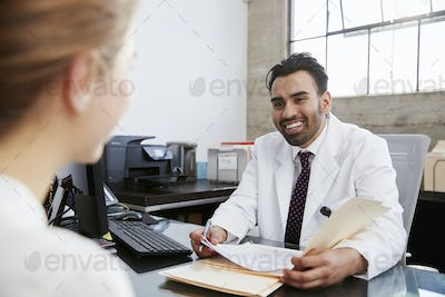 Hispanic male doctor in consultation with female patient