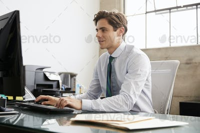 Young white businessman using a computer at an office desk
