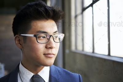 Young Asian businessman looking out of window, close up
