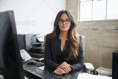 Mixed race woman with long hair and glasses sitting at desk