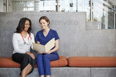 Two female healthcare workers looking at a file together