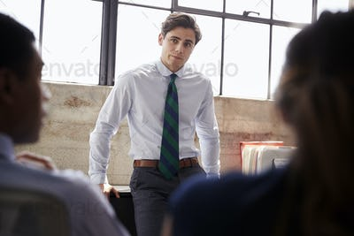 Young male manager listening to team at a meeting, close up