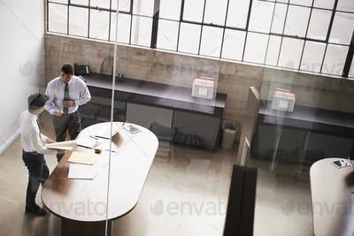 Two businessmen stand talking over paperwork in an office