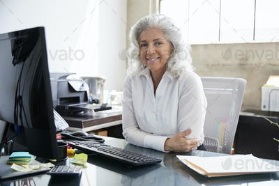 Senior woman sitting at desk in office smiling to camera