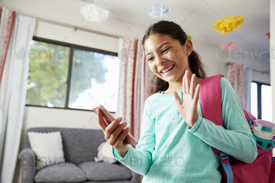 Young Girl With Backpack In Bedroom Ready To Go To School Making Video Call On Mobile Phone