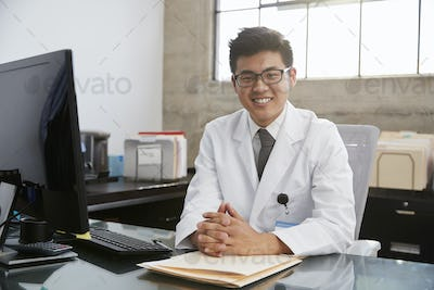 Young Asian male doctor sitting at desk, portrait