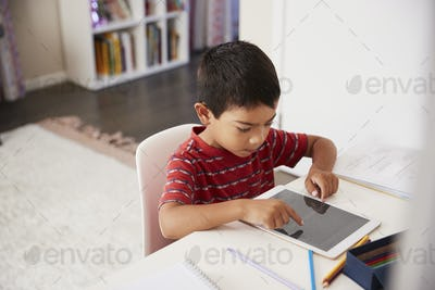 Young Boy Sitting At Desk In Bedroom Using Digital Tablet To Do Homework