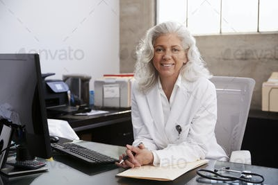 Senior female doctor sitting at desk in an office, portrait